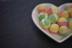 Matfotografi för valentin med en vit maträtt för förälskelsehjärtaform fyllde med godissockersötsaker i gula och röda färger för  Royaltyfria Foton