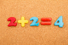 Math Addition. Simple mathematic addition on a cork board background stock photography
