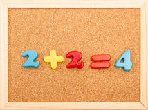 Math Addition. Simple mathematic addition on a wooden frame cork board stock photos