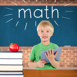 Math against red apple on pile of books in classroom Stock Image