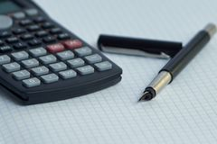 Math calculator and fountain pen lie on white paper close-up stock photography