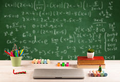 Math class from student school desk. Back to school concept with long numbers calculation on blackboard and a desk with books, fruit Royalty Free Stock Photos