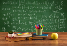 Math class from student school desk. Back to school concept with long numbers calculation on blackboard and a desk with books, fruit Royalty Free Stock Photography