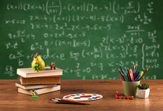 Math class from student school desk. Back to school concept with long numbers calculation on blackboard and a desk with books, fruit Royalty Free Stock Image