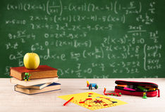 Math class from student school desk. Back to school concept with long numbers calculation on blackboard and a desk with books, fruit Stock Image