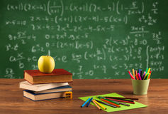 Math class from student school desk. Back to school concept with long numbers calculation on blackboard and a desk with books, fruit Stock Photos