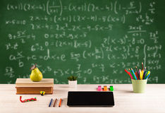 Math class from student school desk. Back to school concept with long numbers calculation on blackboard and a desk with books, fruit Royalty Free Stock Images