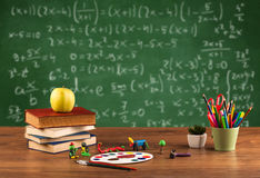 Math class from student school desk. Back to school concept with long numbers calculation on blackboard and a desk with books, fruit Stock Images