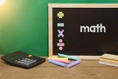 Math concept with calculator on blackboard. stock photo