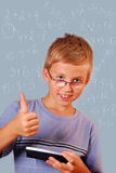 Math is cool. Schoolboy holding calculator and showing thumb up against math blue background Royalty Free Stock Photo