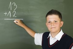 Math is cool!. Young boy standing in front of blackboard and writing. Smiling and looking at camera. Front view Stock Image