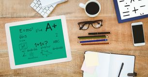 Math equation on digital tablet by stationery. Digital composite of Math equation on digital tablet by stationery royalty free stock image