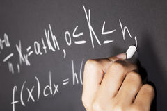 Math equations. Student writing math equation on blackboard Royalty Free Stock Images