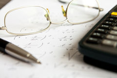 Math exercise with glasses, calculator and pen Stock Image