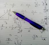 Math exercises. Picture of the pen on the notes with math exercises Stock Photos