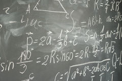 Math formulas on black board. Side view of math formulas written in white chalk on black board background stock images