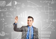 Math formulas. Business man writing math formulas stock photography