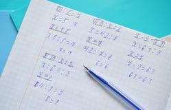 Math homework in a copy-book Royalty Free Stock Photos