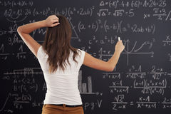 Math isn't easy. Young woman looking at math problem on blackboard Stock Image