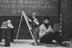 Math lesson. Arithmetic lesson at school. Kid writing on chalkboard while concentrated teacher works on laptop. Side. View sitting men and standing kid back to royalty free stock image