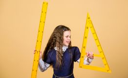 Math lesson. Education and knowledge. small girl back to school. School student learning geometry. Pupil girl with big. Rulers. STEM school disciplines stock photos
