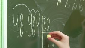 Math lesson at school children solve problems at the blackboard and at their desks. Math lesson at school children in school solve problems on the Board and at stock video footage