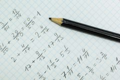 Math problems on graph paper with black pencil.  stock images