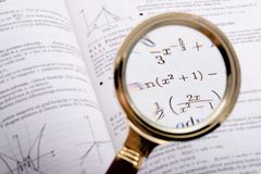 Math reference book detail. Magnifyed with loupe royalty free stock images