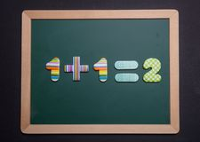 Math simple addition on green board with wooden frame, black background. Math simple addition equation on green board with wooden frame, black background stock photo