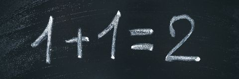 Math simple equation on chalk board. One plus One equals two.  stock images