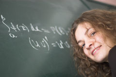 Math student. Female sudent is standing near blackboard with mathematical formulas. Face in focus royalty free stock images