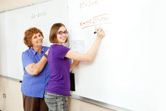 Math Student and Teacher with Copyspace. Math student and teacher working problems on the white board, with blank whiteboard space for text Stock Images