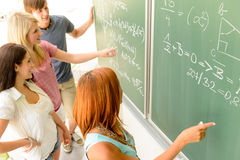Math student write on green chalkboard classmates. Math lesson student write on green chalkboard with classmates pointing Stock Photos