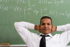 Math teacher. Young confident math teacher sitting in front of chalkboard stock photos