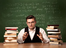 Math teacher at desk. A young ambitious teacher in glasses sitting at classroom desk with pile of books in front of blackboard full of math calculations, numbers Stock Photos
