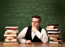 Math teacher at desk. A young ambitious teacher in glasses sitting at classroom desk with pile of books in front of blackboard full of math calculations, numbers Stock Photography