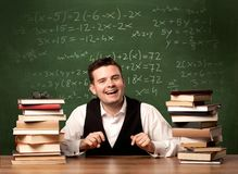 Math teacher at desk. A young ambitious teacher in glasses sitting at classroom desk with pile of books in front of blackboard full of math calculations, numbers Royalty Free Stock Images