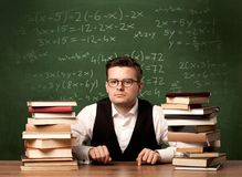 Math teacher at desk. A young ambitious teacher in glasses sitting at classroom desk with pile of books in front of blackboard full of math calculations, numbers Royalty Free Stock Image
