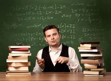 Math teacher at desk. A young ambitious teacher in glasses sitting at classroom desk with pile of books in front of blackboard full of math calculations, numbers Stock Photo