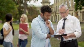 Math teacher explaining difficult task to puzzled male student near university stock photo