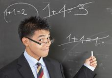 Math teacher pointing error. Smirking Asian math teacher with nerd glasses in suit pointing an elementary wrong addition sum written on a blackboard Royalty Free Stock Photos