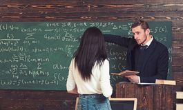 Math teacher pointing at green board. Professor giving explanations to brunette female student. Turn back girl in white royalty free stock photography