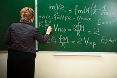 Math teacher writing formula on the blackboard Stock Photo