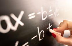 Math teacher writing function, equation or calculation on blackboard in school classroom. stock image
