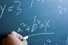 Math Teaching. Teacher writing various high school maths formula on chalkboard stock images