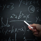 Math Teaching. Teacher writing various high school maths formula on chalkboard stock photography