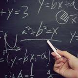 Math Teaching. Teacher writing various high school maths formula on chalkboard stock photo