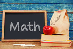 Composite image of math text on white background. Math text on white background against blank blackboard with packed lunch and books royalty free stock photography