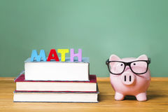 Math theme with pink piggy bank with chalkboard. Mathematics theme with pink piggy bank with chalkboard in the background as concept image of the costs of Stock Photo