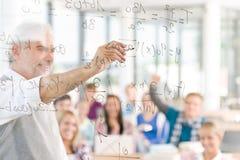 Mathe an der Highschool - Kursteilnehmer mit Professor Stockfoto